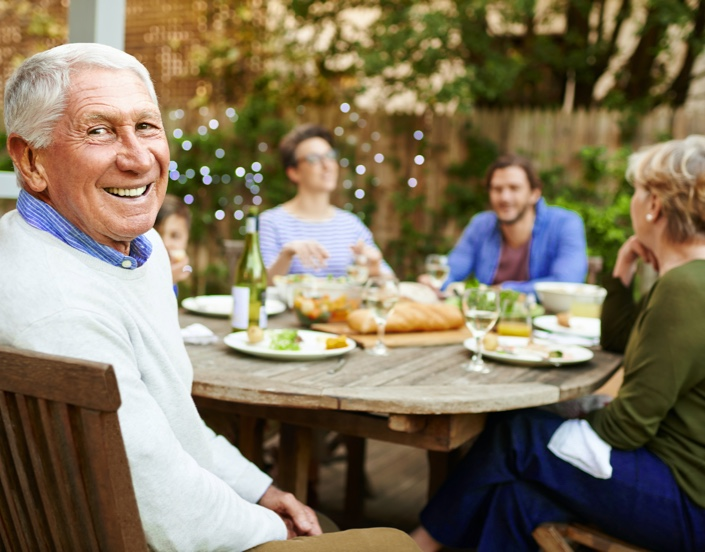 Group of people sitting outside while eating dinner and smiling